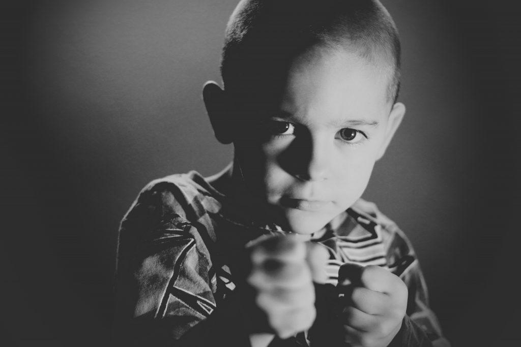 A kid showing his fists representing his character trait; courage