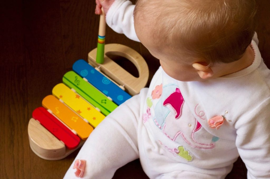 Toddler playing a colorful toy xylophone