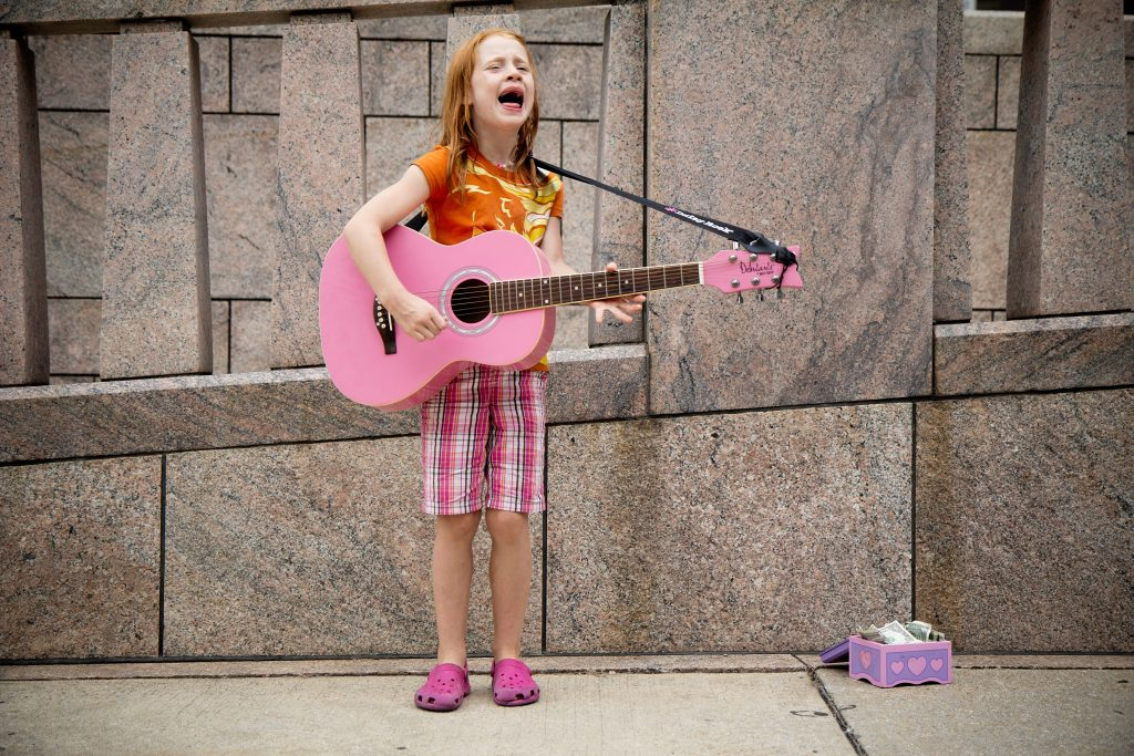 Young girl playing a pink colored guitar in public confidently.