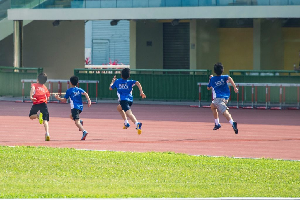 Kids running and exercising on a running track for better health.