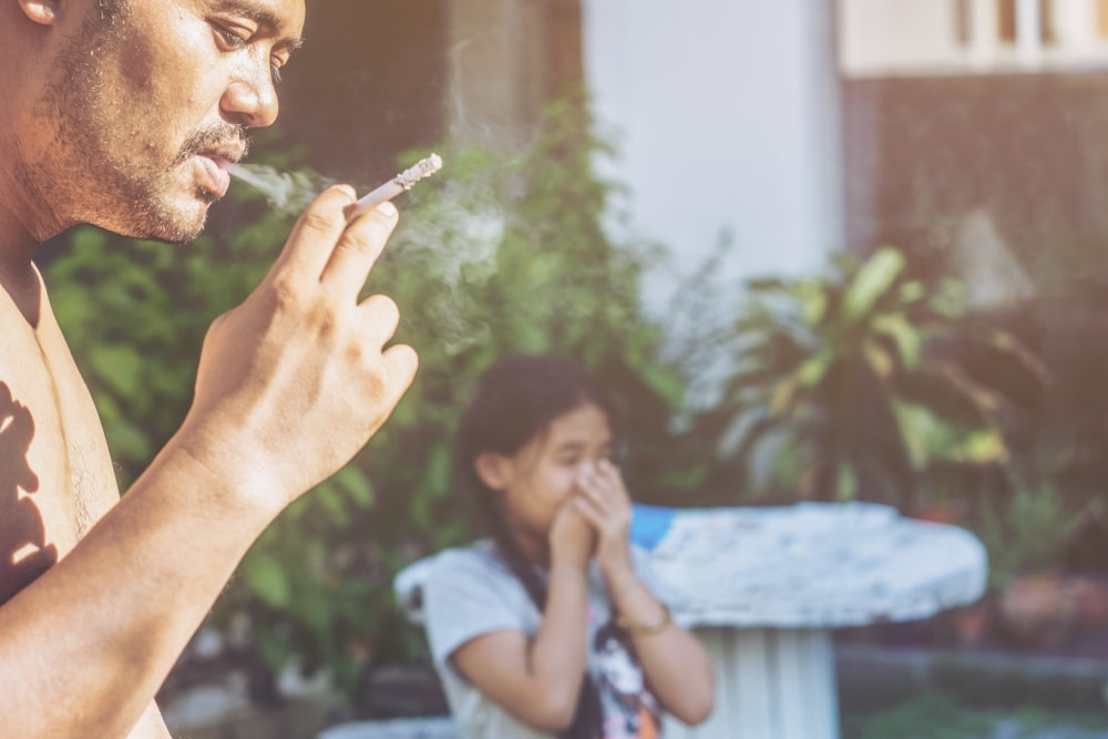 A Dad smoking a cigarette at home in front of his 9 year old daughter.