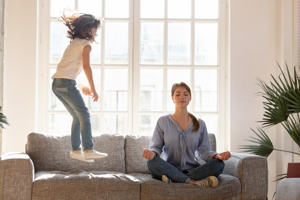 A mother doing yoga ignores her daughters misbehave of jumping on the sofa near her.
