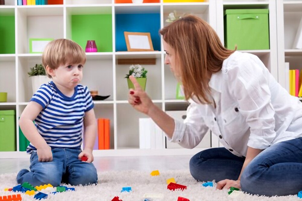 Mother scolding her son playing with blocks